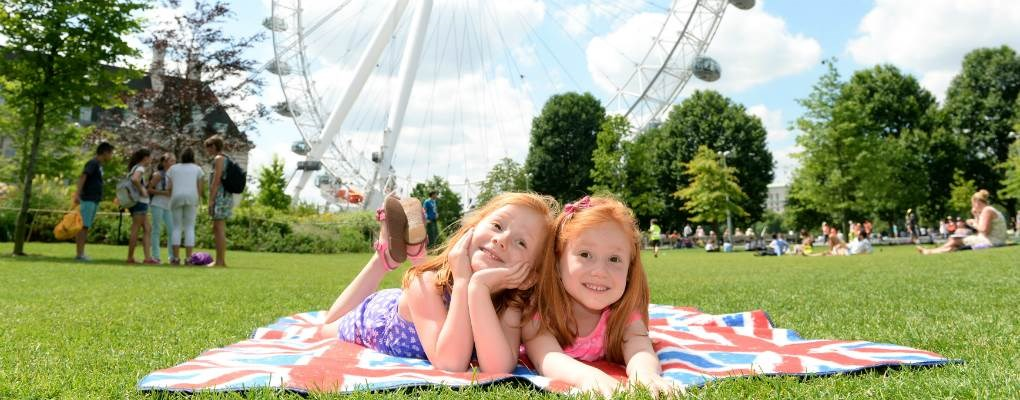 Two twin girls laying on the grass in front of London Eye