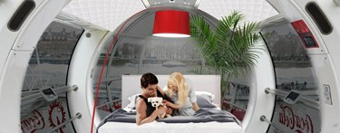 Apartment installed in London Eye with two people on bed
